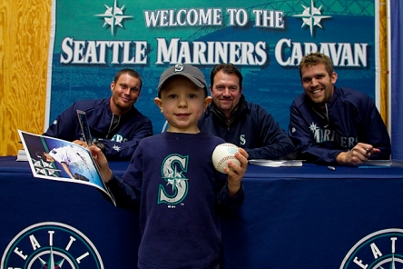 Blake Beavan, Mike Blowers and Tom Wilhelmsen signed autographs for a young fan at the Yakima SunDome during the 2012 Mariners Caravan.