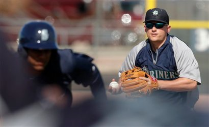 Kyle Seager chases down a runner during the team fundamental drill. (Associated Press/Charlie Riedel)