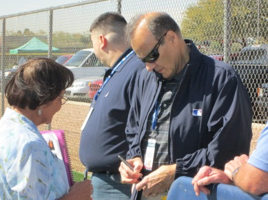 Joe Torre signing autographs while visiting Mariners camp this morning.