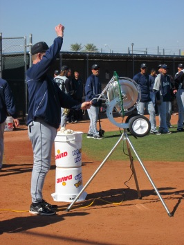 Jeff Datz feeding balls to a pitching machine during pop up drills.