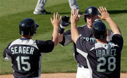 Kyle Seager, Raul Ibanez and Justin Smoak score on Casper Wells' three-run triple. (AP/Charlie Riedel)