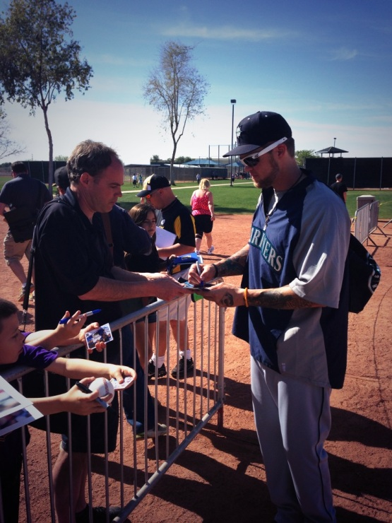 Corey Hart takes time to sign autographs for Mariners fans.