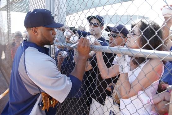 Robinson Cano signs autographs for fans.