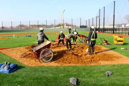 Mariners groundskeeper Tim Wilson helps the crew from the LG Twins in Seoul build a new home plate area