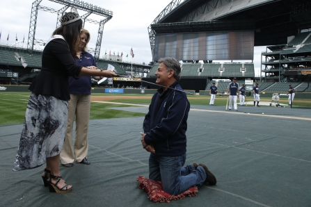 "Mariners broadcaster Rick Rizzs is knighted by Miss Seafair Rio Barber in recognition of his ""contributions to Seattle's quality of life."""
