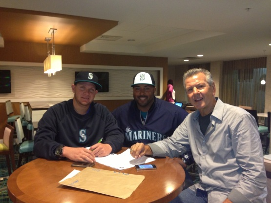 Misael Siverio (left) signing his contract next to Mariners scout Noel Sevilla.