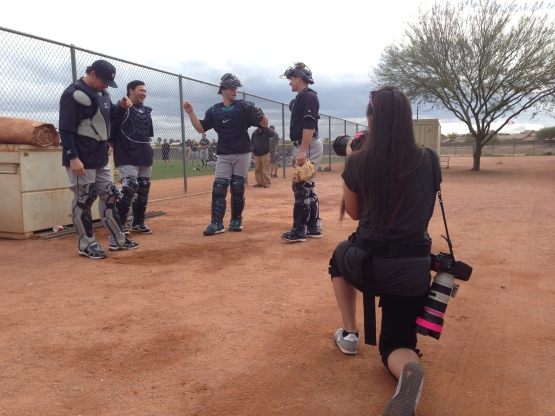 Seattle Times photographer Bettina Hansen sets up for a shot of catchers John Baker, Jesus Sucre, Mike Zunino and John Hicks.