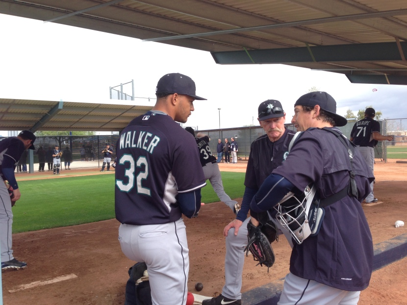 Taijuan Walker consults with catcher John Baker and pitching coach Rick Waits after his bullpen session.
