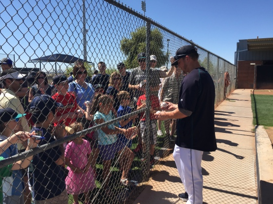 Kyle Seager signs autographs by the bullpen area.