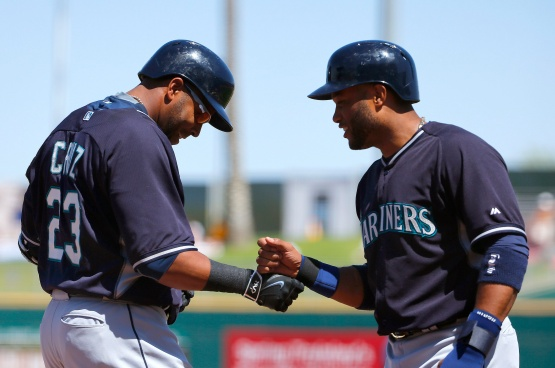Seattle Mariners' Nelson Cruz (23) smiles as he celebrates his two-run home run against the Cleveland Indians with Robinson Cano, right, during the first inning of a spring training baseball game Tuesday, March 31, 2015, in Goodyear, Ariz. (AP Photo/Ross D. Franklin)