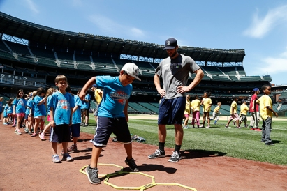 Infielder Chris Taylor leads Boys & Girls Club members through some agility drills at PLAY.