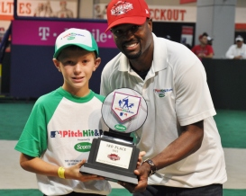 MLB Network's Harold Reynolds presents a Third Place plaque to Trevor Cogley of Hayden, Idaho, who represented the Mariners at the Pitch, Hit and Run National Finals in Cincinnati