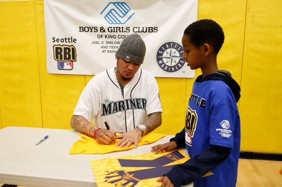 Felix Hernandez signs an autograph for a young baseball player at the Smilow Clubhouse & Teen Center at Rainier Vista.