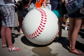 Fans wait in line next to a baseball sculpture to enter the stadium for a spring training baseball game between the San Francisco Giants and the Seattle Mariners Wednesday, March 16, 2016, in Peoria, Ariz. (AP Photo/Jae C. Hong)