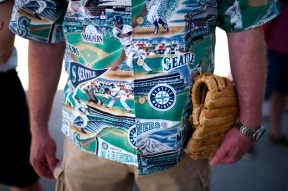 A Seattle Mariners fan waits in line outside a stadium to attend the Mariners' spring training baseball game against the San Francisco Giants Wednesday, March 16, 2016, in Peoria, Ariz. (AP Photo/Jae C. Hong)