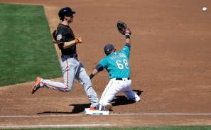 San Francisco Giants' Kelby Tomlinson, left, takes first base as Seattle Mariners first baseman Efren Navarro misses the throw during the second inning of a spring training baseball game Wednesday, March 16, 2016, in Peoria, Ariz. (AP Photo/Jae C. Hong)