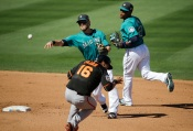 Seattle Mariners shortstop Shawn O'Malley, center, throws the ball to first base after forcing out San Francisco Giants' Angel Pagan as teammate Robinson Cano, right, helps cover second base during the fifth inning of a spring training baseball game, Wednesday, March 16, 2016, in Peoria, Ariz. (AP Photo/Jae C. Hong)