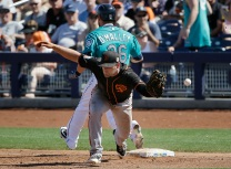 Seattle Mariners' Shawn O'Malley safely takes first base as San Francisco Giants first baseman Conor Gillaspie misses the throw from third baseman Kelby Tomlinson during the third inning of a spring training baseball game Wednesday, March 16, 2016, in Peoria, Ariz. (AP Photo/Jae C. Hong)