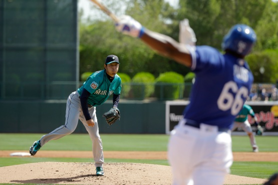 Los Angeles Dodgers' Yasiel Puig, foreground, swings on a pitch from Seattle Mariners starting pitcher Hisashi Iwakuma, of Japan, during the first inning a spring training baseball game Monday, March 21, 2016, in Phoenix . (AP Photo/Jae C. Hong)
