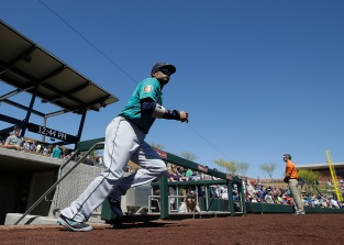 Seattle Mariners' Robinson Cano runs out of the dugout to stretch before a spring training baseball game against the Colorado Rockies, Thursday, March 24, 2016, in Scottsdale, Ariz. (AP Photo/Darron Cummings)