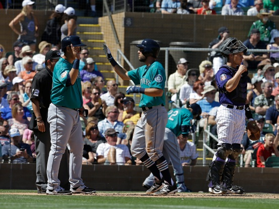 Seattle Mariners' Chris Taylor is congratulated by Dae Ho Lee after scoring on a hit by Seth Smith during the second inning of a spring training baseball game Thursday, March 24, 2016, in Scottsdale, Ariz. Colorado Rockies catcher Dustin Garneau is at right. (AP Photo/Darron Cummings)
