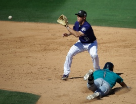 Colorado Rockies' DJ LeMahieu takes the throw as Seattle Mariners' Chris Taylor advances to second on a wild pitch during the fifth inning of a spring training baseball game Thursday, March 24, 2016, in Scottsdale, Ariz. (AP Photo/Darron Cummings)