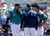 Seattle Mariners starting pitcher Felix Hernandez, left, meets on the mound with catcher Chris Iannetta, right, and a coach during the first inning of a spring training baseball game against the San Diego Padres in Peoria, Ariz., Wednesday, March 30, 2016. (AP Photo/Jeff Chiu)