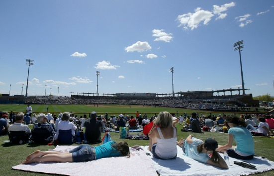 Fans watch from the outfield lawn during the fifth inning of a spring training baseball game between the Seattle Mariners and the San Diego Padres in Peoria, Ariz., Wednesday, March 30, 2016. (AP Photo/Jeff Chiu)