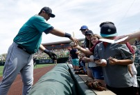 Seattle Mariners' Dae Ho Lee, from Korea, signs autographs for fans before a spring training baseball game against the Arizona Diamondbacks in Scottsdale, Ariz., Monday, March 14, 2016. (AP Photo/Jeff Chiu)