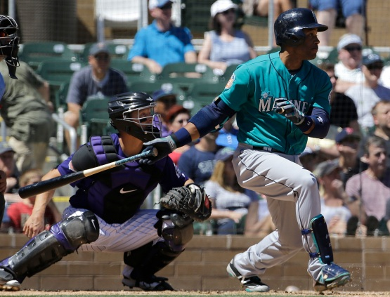Seattle Mariners' Robinson Cano, right, hits a run-scoring double in front of Colorado Rockies catcher Nick Hundley during the third inning of a spring training baseball game in Scottsdale, Ariz., Saturday, April 2, 2016. (AP Photo/Jeff Chiu)