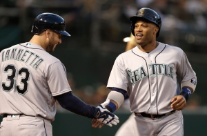 Seattle Mariners' Robinson Cano, right, is congratulated by Chris Iannetta, left, after scoring against the Oakland Athletics in the fourth inning of a baseball game Monday, May 2, 2016, in Oakland, Calif. (AP Photo/Ben Margot)