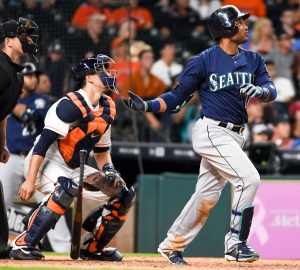 Seattle Mariners' Robinson Cano, right, watches his go-ahead solo home run in the tenth inning of a baseball game against the Houston Astros, Saturday, May 7, 2016, in Houston. (AP Photo/Eric Christian Smith)
