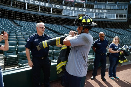 Nelson Cruz swaps his baseball uniform for a Seattle Fire jacket and helmet.