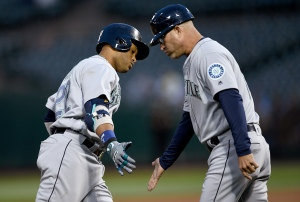 OAKLAND, CA - MAY 03:  Robinson Cano #22 of the Seattle Mariners is congratulated by third base coach after Cano hit a solo home run against the Oakland Athletics in the top of the fourth inning at O.co Coliseum on May 3, 2016 in Oakland, California.  (Photo by Thearon W. Henderson/Getty Images)