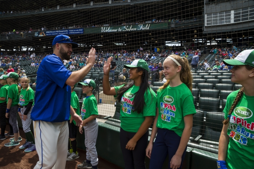 Kaiea Higa, who is representing the Mariners at the National Pitch, Hit & Run Championships at Petco Park, gets a high five from pitcher Nathan Karns.