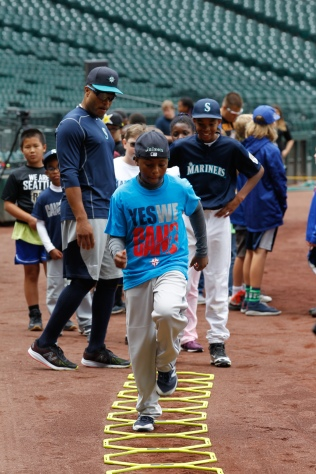 Robinson Cano helps put kids through an agility drill during PLAY, a program that promotes healthy, active lifestyles for kids.